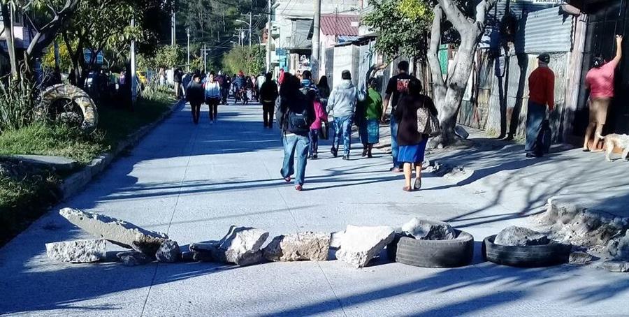 Vecinos de El Búcaro bloquean el paso de vehículos para manifestar contra los hechos de violencia en el sector. (Foto Prensa Libre: Dalia Santos)