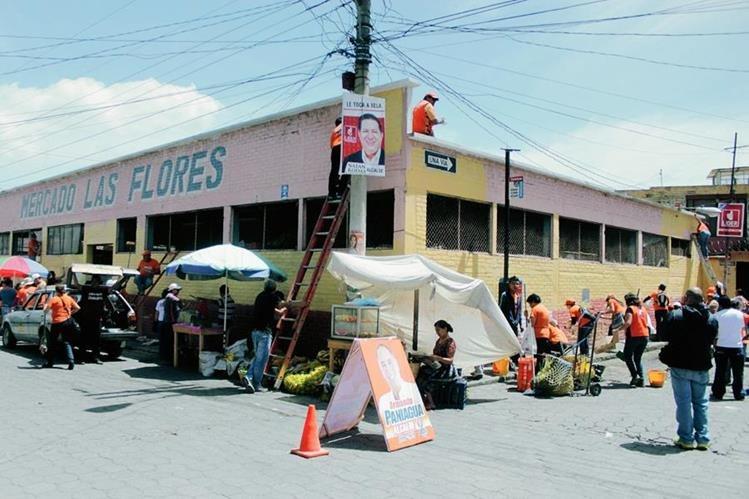 Seguidores de candidatos a la Alcaldía de la ciudad de Quetzaltenango pintan el mercado Las Flores. (Foto Prensa Libre: Carlos Ventura)