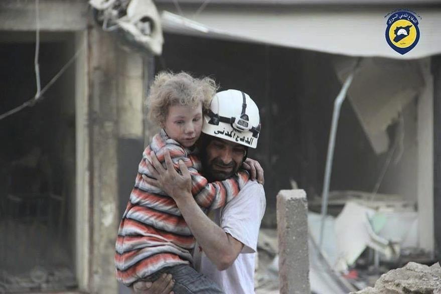 Un rescatista llora conmovido al rescatar a un niño de los escombros en Siria. (Foto Prensa Libre: EFE)