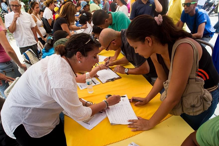 Una mujer firma para en apoyo a la reactiviación del proceso revocatorio al mandato del presidente de Venezuela Nicolás Maduro en Caracas. (Foto Prensa Libre: EFE).