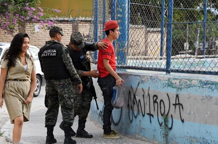 Efectivos de la Policía Militar registran a un hondureño durante un operativo el barrio El Bosque. (Foto Prensa Libre:AFP).