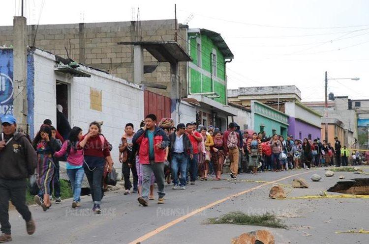 Pobladores pasan a pie junto a socavamiento para buscar algún medio de transporte que los lleve a su destino. (Foto Prensa Libre: Héctor Cordero).