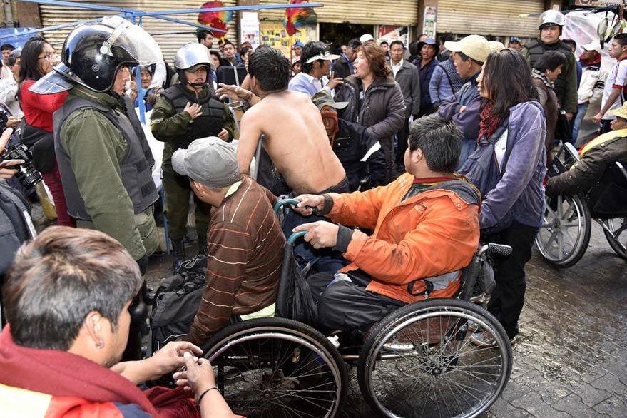 Discapacitados se enfrentan a la policía boliviana en La Paz. (Foto Prensa Libre: AFP).