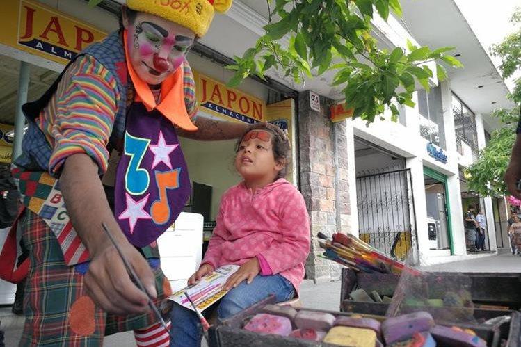 """El payaso """"Zancudito Show"""" maquilla el rostro de Brithany Cruz Morales, de 4 años, en el Paseo de la Sexta, zona 1 de la capital. (Foto Prensa Libre: César Pérez)"""