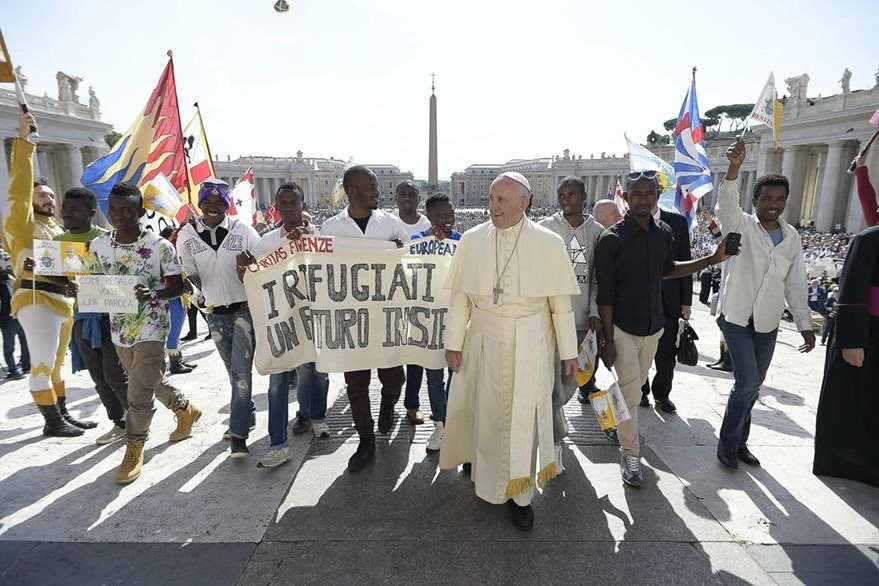 El Papa camina junto a un grupo de refugiados durante la celebración de la audiencia general en la Plaza de San Pedro del Vaticano. (Foto Prensa Libre: EFE).
