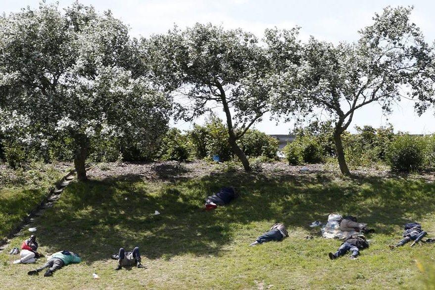 Inmigrantes descansan en un terreno situado cerca de la entrada del Eurotúnel, en Coquelles, cerca de Calais, Francia. (Foto Prensa Libre: EFE).
