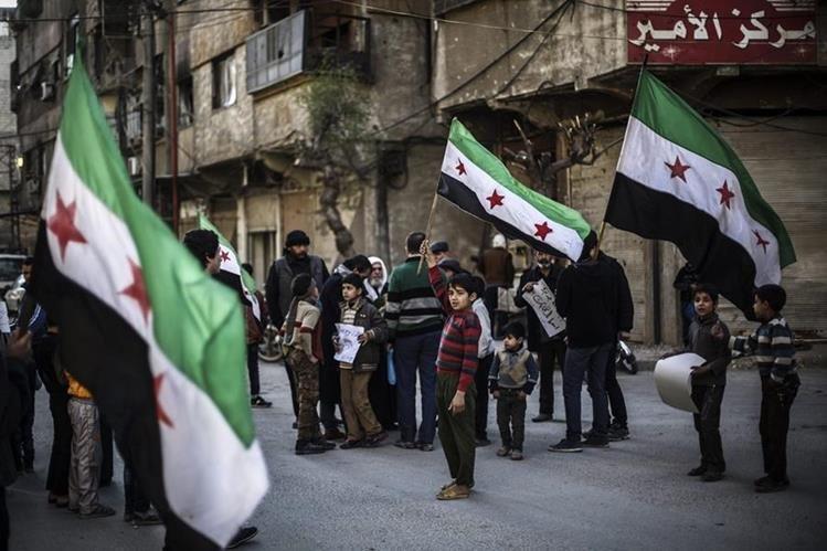 Un niño ondea la bandera de Siria, azotada por la guerra desde hace cinco años. (Foto Prensa Libre: EFE).