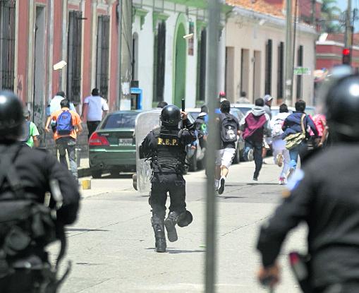 Un grupo de estudiantes huyen mientras le lanzan piedras a un grupo de policías antimotines, en la zona 1. (Foto Prensa Libre: Hemeroteca PL)