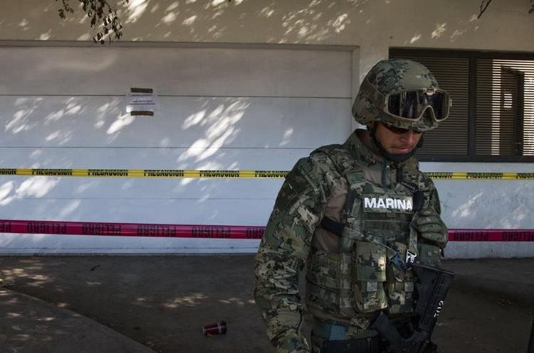 """A marine stands guard outside the house where five gang suspects were killed in the military operation which resulted in the recapture of Joaquin """"El Chapo"""" Guzman on January 8 in the city of Los Mochis, Sinaloa State, Mexico, on January 10, 2016. Mexican marines recaptured fugitive drug kingpin Joaquin """"El Chapo"""" Guzman on January 8 in the northwest of the country, six months after his spectacular prison break embarrassed authorities. AFP PHOTO/HECTOR GUERRERO"""
