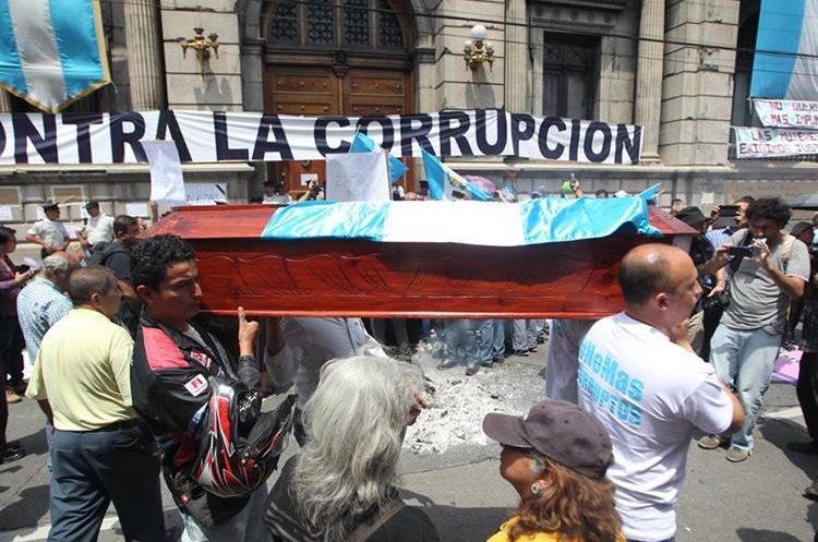 Manifestantes cargan un ataúd como señal de repudio hacia los diputados. (Foto Prensa Libre: Érick Ávila)