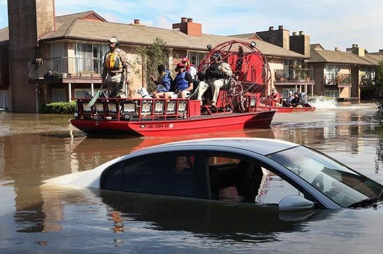 Rescatistas ayudan a los residentes a abndonar un complejo de apartamentos en Houston,Texas.(AFP).