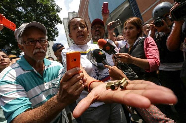 La diputada Gaby Arellano muestra a la prensa cartuchos de bala disparados por civiles encapuchados contra marcha. (Foto Prensa Libre: EFE)