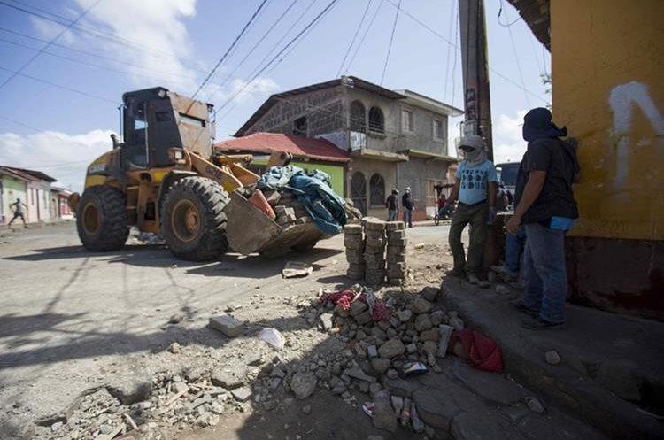 Grupo de simpatizantes del Gobierno de Ortega levantan adoquines de una barricada en Monimbo, Masaya. (EFE)