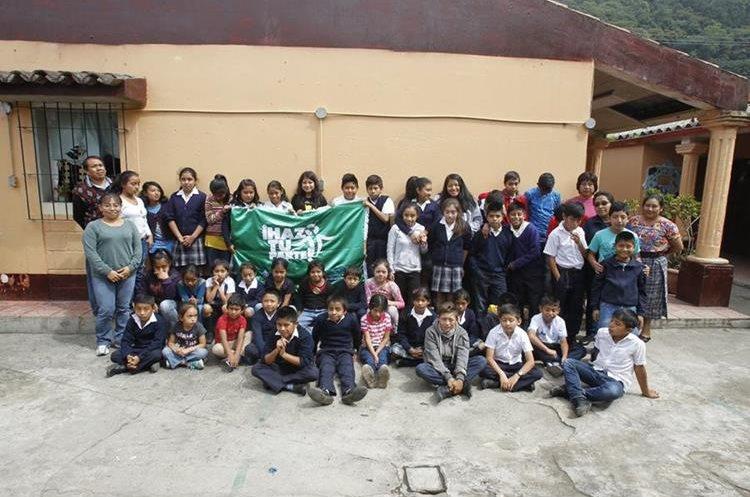 Estudiantes de la escuela de San Cristóbal El Bajo muestran la bandera verde que ganaron gracias al reciclaje.