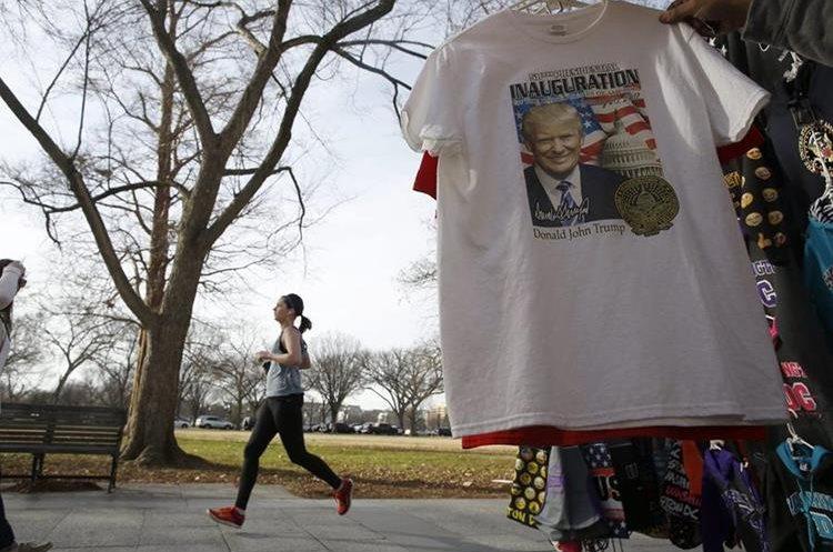 Una joven corre junto a un puesto callejero de artículos de Trump en Washington.