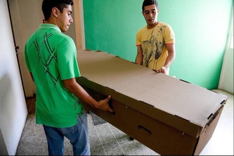 Los altos costos de los materiales obligan a muchos a comprar un ataúd de cartón. (Foto Prensa Libre: AFP)