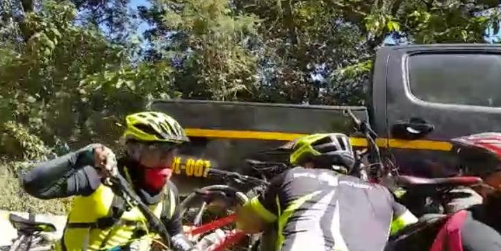 Ciclistas se resguardan de posibles balas perdidas en la ruta entre San Pedro La Laguna y Santiago Atitlán. (Foto Prensa Libre).