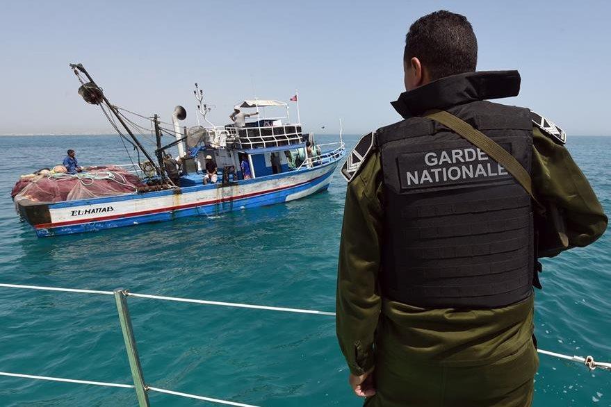 Un guardia costero vigila una sencilla embarcación, cuyos ocupantes están por ser rescatados. (Foto Prensa Libre: AFP).