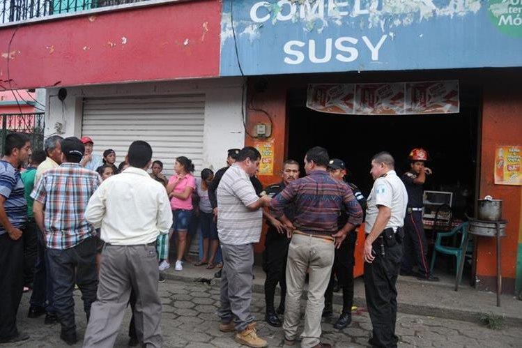 Agentes de la PNC hablan con vecinos frente al negocio donde fue ultimado el expolicía Víctor Adán Vargas Maldonado, en Flores Costa Cuca. (Foto Prensa Libre: Alexánder Coyoy)