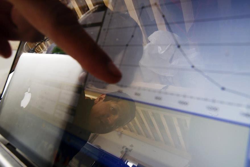 El científico Raul Cordero examina valores de medición en un ordenador portátil en el campamento Glaciar Unión. (Foto Prensa Libre: EFE).