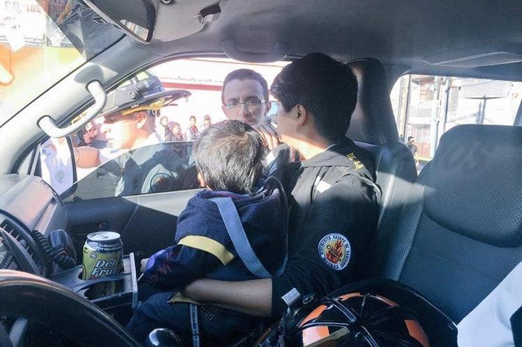 Un Bombero Voluntario cuida al pequeño de dos años que sobrevivió al ataque contra su madre. (Foto Prensa Libre: CBV)