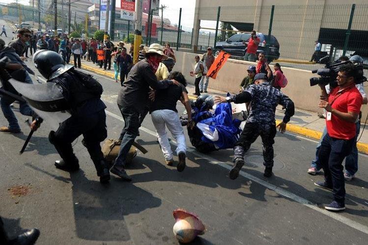 Manifestantes se enfrentan a la Policía en los alrededores de la Casa Presidencial de Honduras donde exigían justicia por la muerte de la activista Berta Cáceres. (Foto Prensa Libre: AFP).
