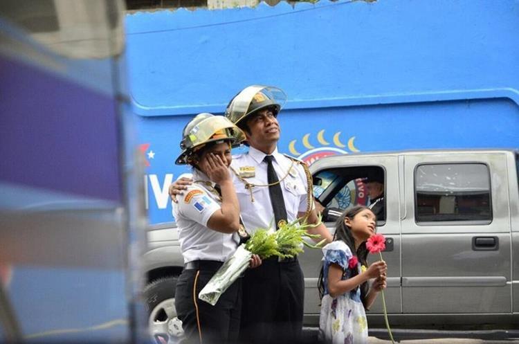 Marina y su hija Samantha, observan el cartel con el cual Carlos le pidió matrimonio, que desplegaron en la Estación de Bomberos Voluntarios en Quetzaltenango. (Foto, Prensa Libre: Stereo 100)