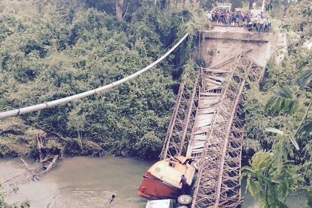 Vecinos de la comunidad Cruce El Rosario observan un tráiler que cayó al vacío cuando colapsó el puente que une a comunidades de Dolores y Melchor de Mencos, Petén. (Foto Prensa Libre: Rigoberto Escobar)