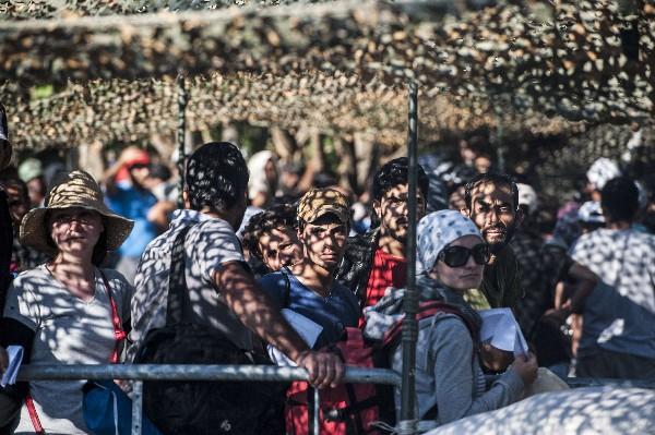 Inmigrantes esperan a ser registrados en un centro de refugiados en Presevo.