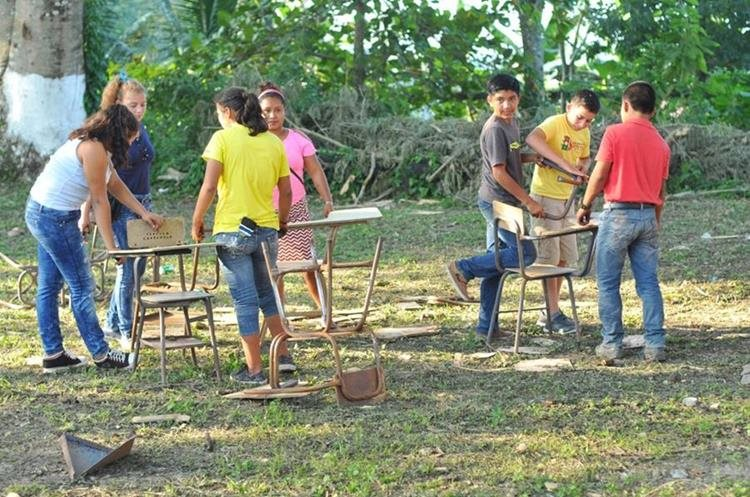 Estudiantes recolectan escritorios dañados, los cuales serán restaurados. (Foto Prensa Libre: Rigoberto Escobar)