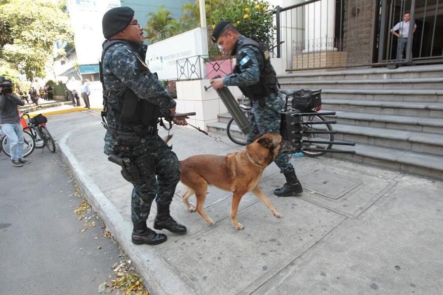 La policía asistida por un agente K9 revisa el edificio en busca de explosivos. (Foto Prensa Libre: Erick Ávila)