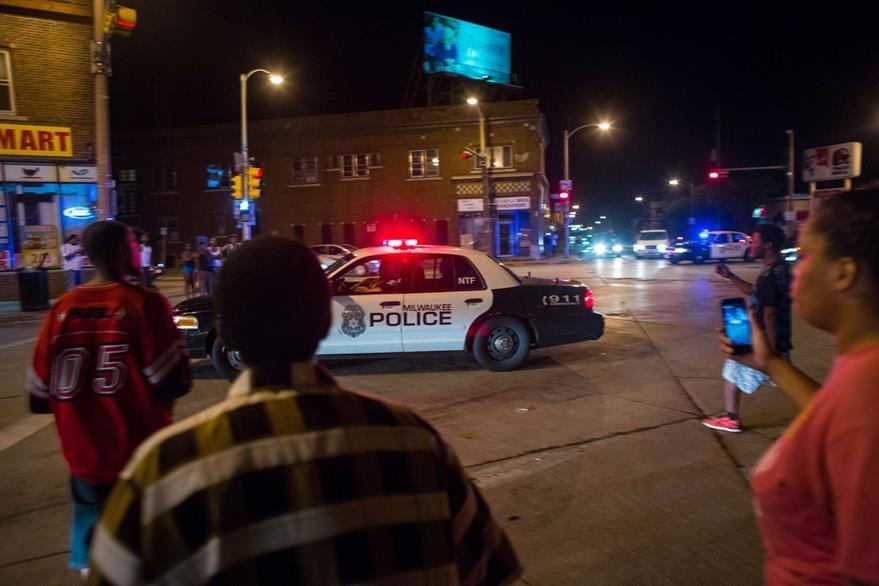 Descontentos acosan a una patrulla, en Milwaukee. (Foto Prensa Libre: AFP)