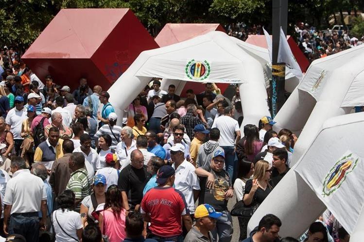 Decenas de personas participan en el acto de recolección de firmas para activar el proceso revocatorio al mandato del presidente de Venezuela Nicolás Maduro en Caracas. (Foto Prensa Libre: EFE).
