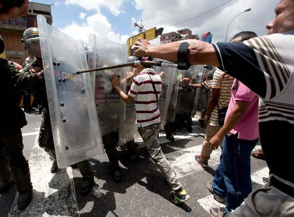 Manifestantes empujan la Guardia Nacional y demanda alimentos cerca de Caracas.(AFP).