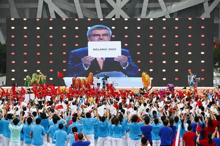 Cientos de personas festejaron la elección de Pekín como sede de los Juegos de Invierno ante el anuncio de Thomas Bach. (Foto Prensa Libre: EFE)