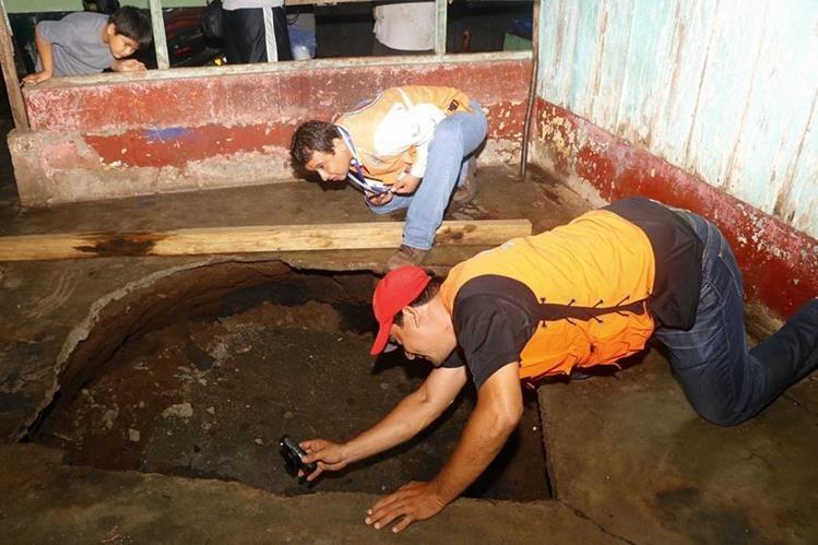 Personal de la Conred evalúa el diámetro del agujero que se formó en una vivienda del barrio Monterrey, zona 4 de Retalhuleu. (Foto Prensa Libre: Rolando Miranda)