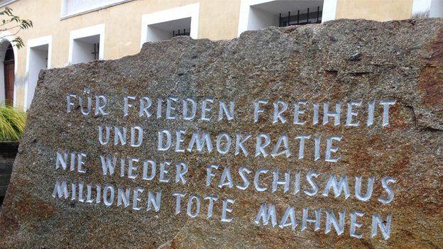 """Piedra memorial que se erige a pocos pasos de la casa de Hitler. Image caption A pocos pasos de la casa donde nació Hitler hay un memorial con la inscripción: """"Por la paz, la democracia y la libertad. Millones de muertos nos recuerdan que nunca más debe de haber fascismo""""."""