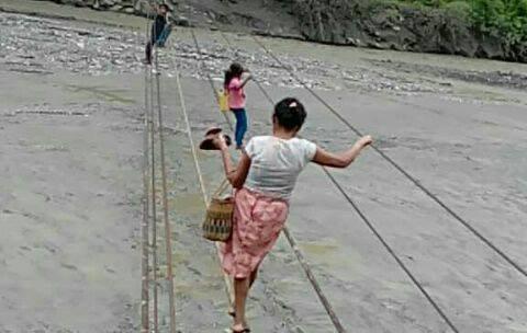 Algunas personas utilizan los cables que quedaron del puente de hamaca para cruzar el río San Vicente, en El Solís, Cabañas, Zacapa. (Foto Prensa Libre: Mario Morales)