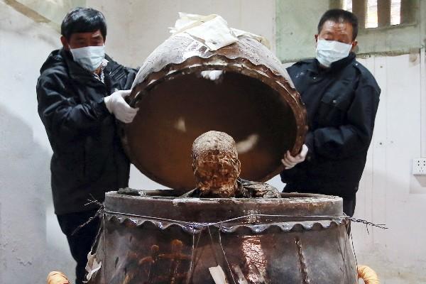Expertos muestran la vasija que contiene el cuerpo momificado de Fu Hou. (AP.