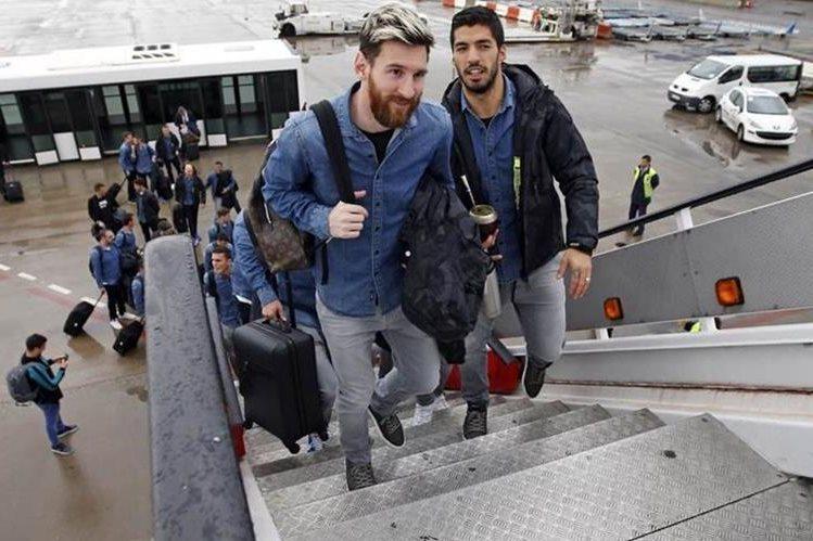 El argentino Lionel Messi y el uruguayo Luis Suárez abordan el avión que los trasladó hasta Escocia. (Foto Prensa Libre: FC Barcelona)