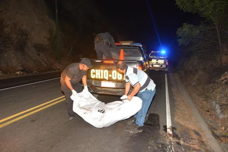 El cadáver carbonizado de un hombre, localizado en la ruta entre Chiquimula y Zacapa, es retirado del lugar donde fue abandonado. (Foto Prensa Libre: Víctor Gómez)