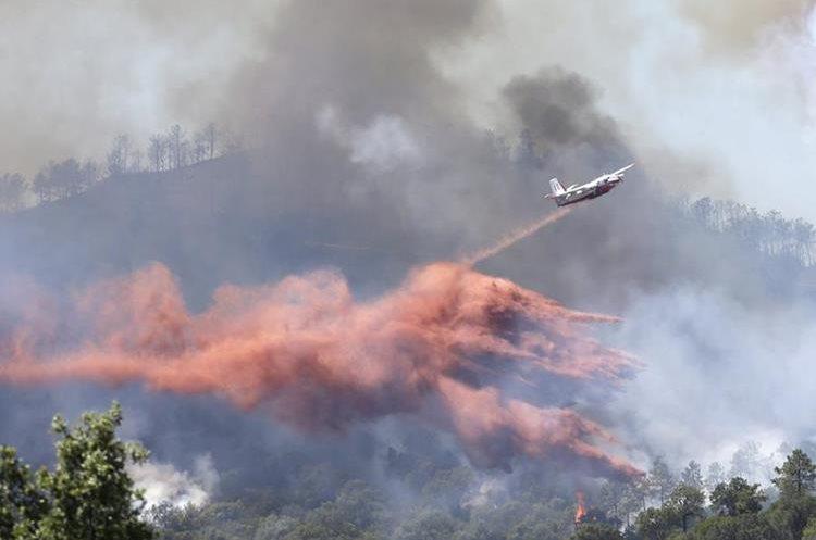Un avión cisterna participa en las operciones para apager el fuego. (AP).