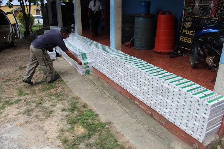 Un agente de la PNC contabiliza cigarrillos decomisados en El Chal, Petén. (Foto Prensa Libre: Walfredo Obando)