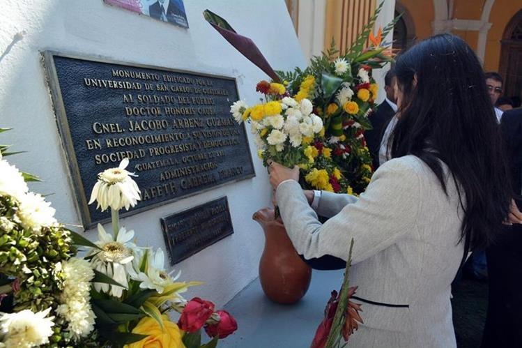La ministra de Salud, Lucrecia Hernández, coloca una ofrenda floral en la tumba de Jacobo Arbenz Guzmán. El florero tiene arena mojada en lugar de agua. (Foto Prensa Libre: Ministerio de Salud)