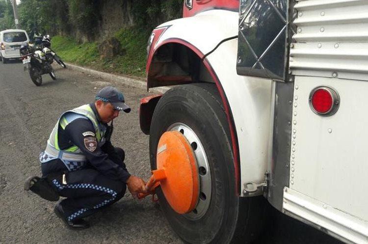 Un agente de la PMT de Villa Nueva inmoviliza un autobús por tener multas pendientes desde el año pasado. (Foto Prensa Libre: Dalia Santos)