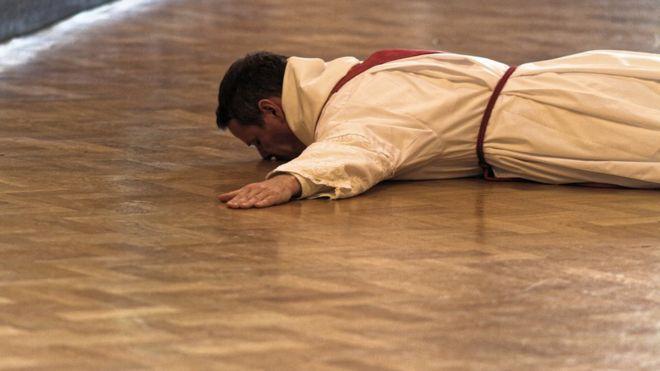 Philip Mulryne postrado en el suelo durante la ceremonia para ordenarse como sacerdote en la iglesia Saint Saviour de Dublin. (PHILIP MCSHANE)