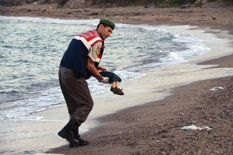 Un oficial de la policía turca, rescata el cadáver del menor que fue hallado en las costas del Mediterráneo de Bodrum, Turquía, la madrugada de este miércoles. (Foto Prensa Libre: AP).