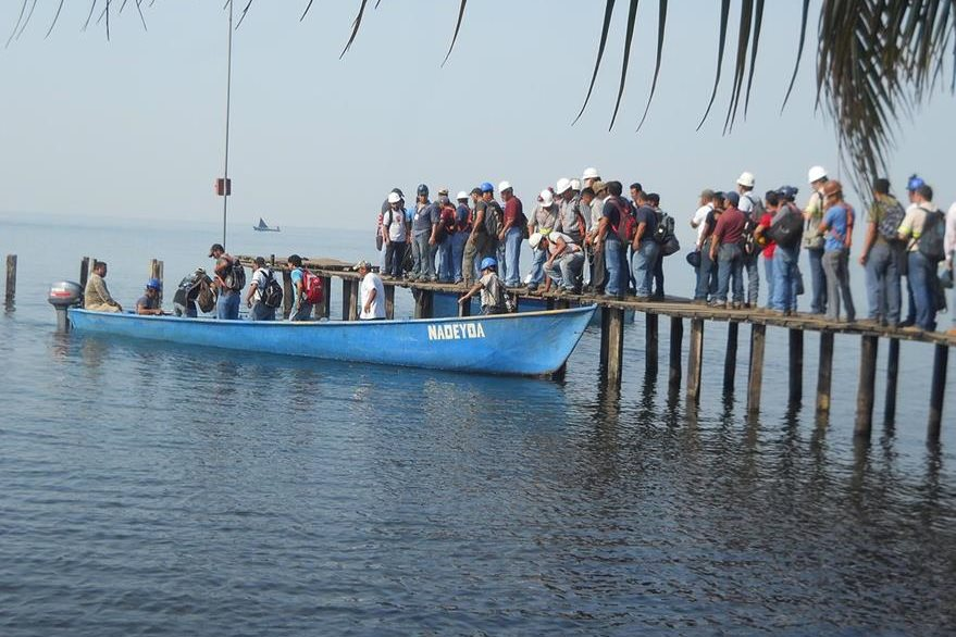 Trabajadores de la mina abandonan el lugar vía marítima. (Foto Prensa Libre: Dony Stewart).