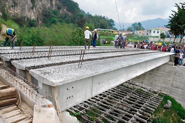 Pobladores de   Sololá observan las cinco vigas reforzadas para la reconstrucción del puente El Molino, destruido en el 2005 por la tormenta Stan. (Foto Prensa Libre: Édgar René Sáenz)