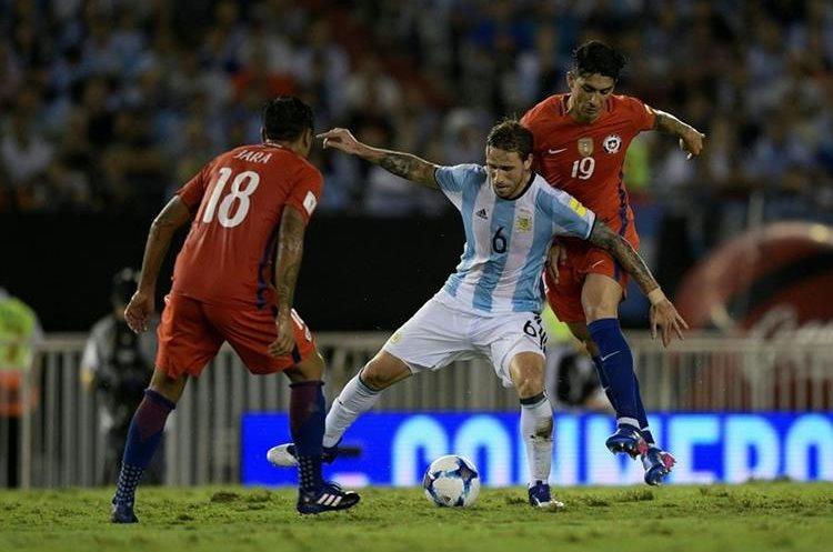 Lucas Biglia intenta cubrir la pelota ante la marca de dos jugadores chilenos.